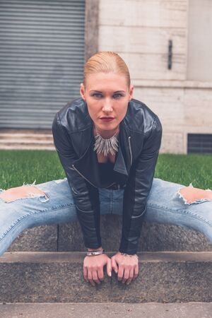 ripped jeans: Beautiful blonde girl wearing ripped jeans and leather jacket posing in the city streets