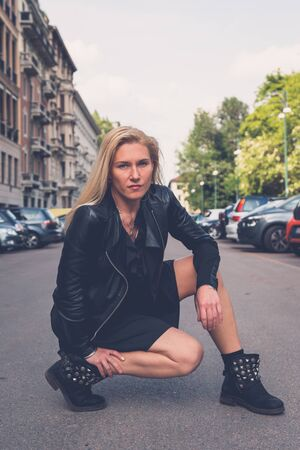 seductive expression: Beautiful blonde girl with black minidress and leather jacket posing in the city streets Stock Photo
