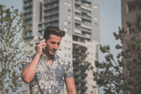 short sleeve: Young handsome man wearing a short sleeve shirt and talking on phone in an urban context Stock Photo