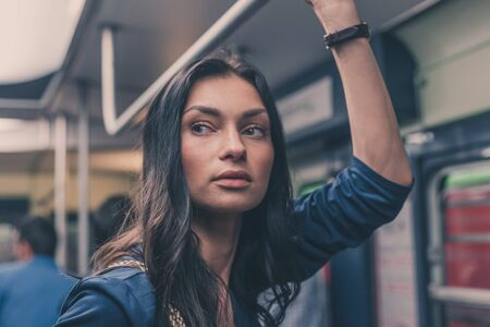 attractive female: Gorgeous young brunette posing in a metro car Stock Photo
