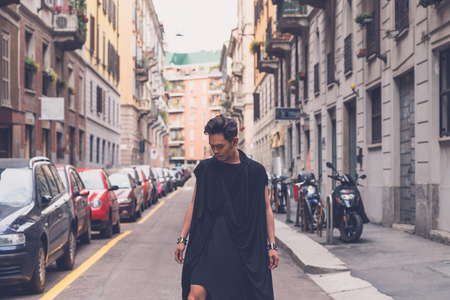 filipino adult: Young handsome Asian model dressed in black tunic posing in the city streets Stock Photo