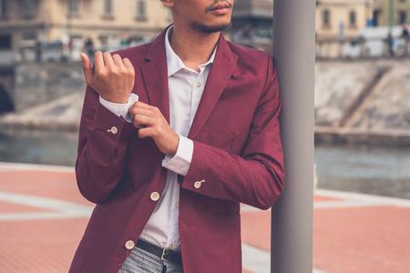Giovane modello asiatico bello vestito di rosso giacca sportiva che propone da un bacino rtificial