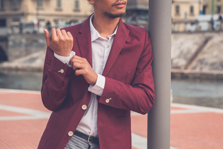 Young handsome Asian model dressed in red blazer posing by an rtificial basin