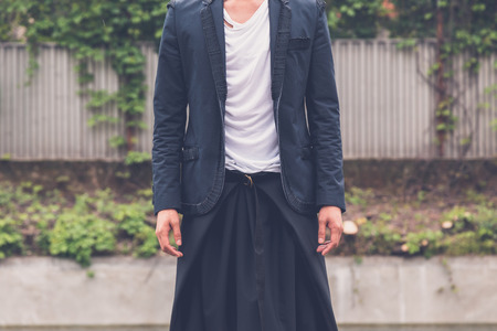 philippine adult: Detail of a young handsome Asian model dressed in black posing in the city streets Stock Photo