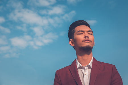 philippine adult: Young handsome Asian model dressed in red blazer posing in the city streets Stock Photo