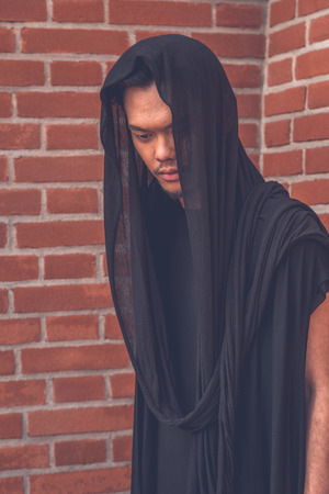 philippine adult: Young handsome Asian model dressed in black tunic posing with a brick wall in background Stock Photo