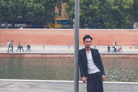 filipino adult: Young handsome Asian model dressed in black posing by an urban artificial basin