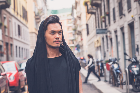 philippine adult: Young handsome Asian model dressed in black tunic posing in the city streets Stock Photo