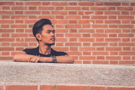 tunic: Young handsome Asian model dressed in black tunic posing with a brick wall in background Stock Photo