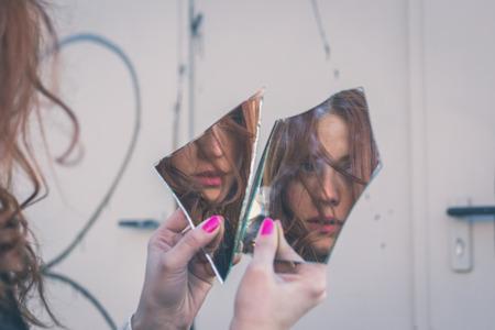 pelirrojas: Hermosa chica pelirroja con el pelo largo y ojos azules mirando a s� misma en un espejo roto