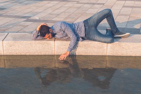 Beau jeune homme avec les cheveux courts portant une cravate d'arc et se regardant dans l'eau