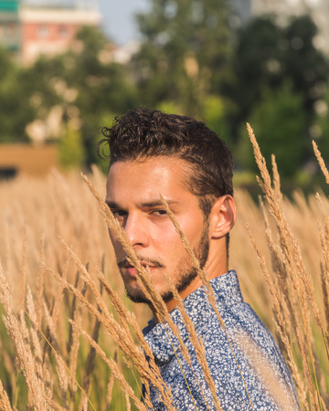lonely boy: Young handsome man with short hair posing in a field Stock Photo