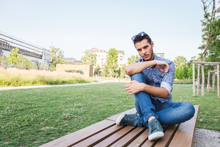 Young handsome man with short hair sitting on a bench in a city park