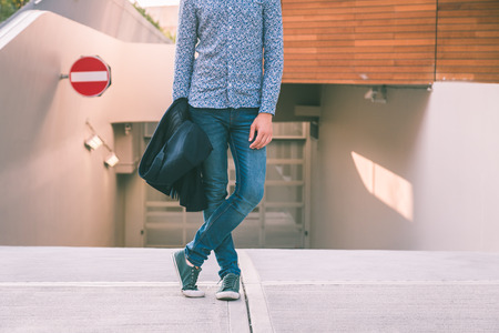 shirtsleeves: Detail of a young handsome man in shirtsleeves hair posing in the city streets Stock Photo