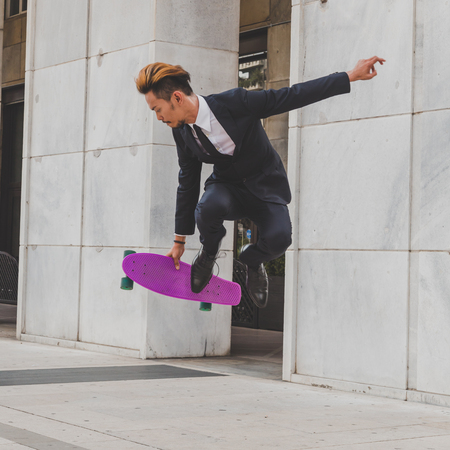 boy skater: Young handsome Asian model dressed in dark suit and tie jumping with his skateboard