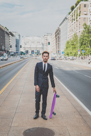 skater boy: Young handsome Asian model dressed in dark suit and tie posing with his skateboard