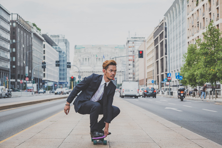 cute guy: Young handsome Asian model dressed in dark suit and tie riding his skateboard