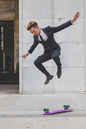 funny guys: Young handsome Asian model dressed in dark suit and tie jumping with his skateboard
