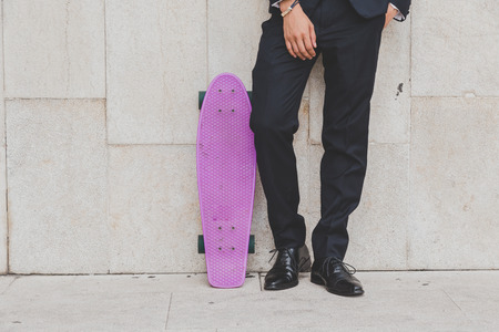 skater boy: Detail of a young model dressed in dark suit posing with his skateboard Stock Photo