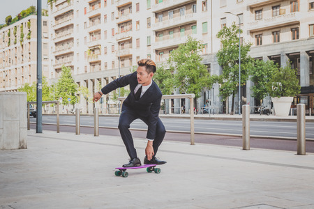 asian style: Young handsome Asian model dressed in dark suit and tie posing with his skateboard