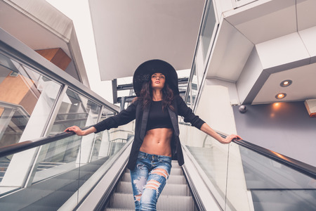 gorgeous woman: Gorgeous young brunette with hat posing on an escalator