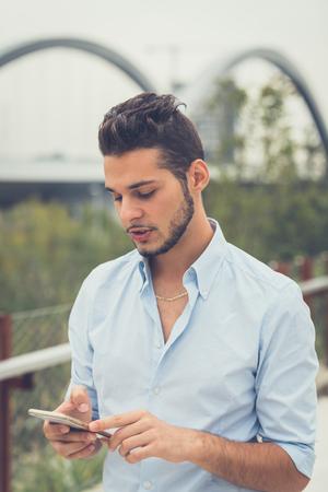Giovane uomo bello con i capelli corti e la barba sms mentre posa in un contesto urbano