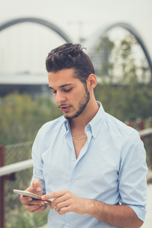 Young handsome man with short hair and beard texting while posing in an urban context
