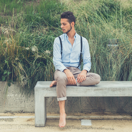 bare feet boys: Young handsome man with short hair and beard wearing suspenders and sitting on a concrete bench