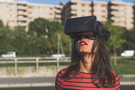 headset woman: Beautiful young brunette with long hair wearing virtual reality headset in an urban context