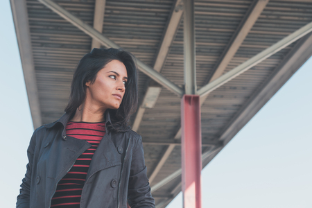 modern girl: Beautiful young brunette with long hair posing in an urban context
