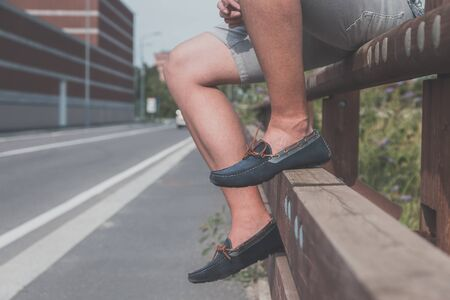 boy feet: Detail of a young handsome man wearing loafers and posing in an urban context Stock Photo