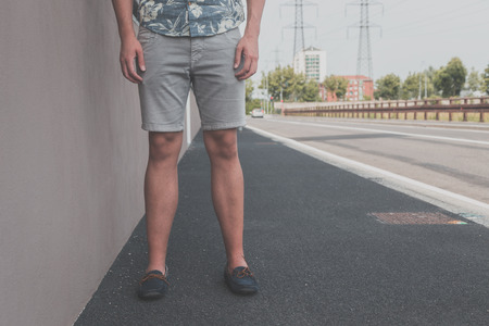 Detail of a young handsome man wearing shorts and posing in an urban context Stock Photo