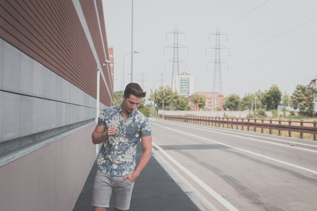 lonely boy: Young handsome man with short hair wearing a short sleeve shirt and posing in an urban context Stock Photo