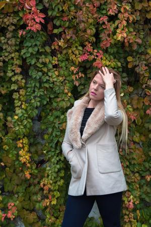 gente triste: Hermosa joven con la presentaci�n larga del pelo rubio en un contexto urbano Foto de archivo
