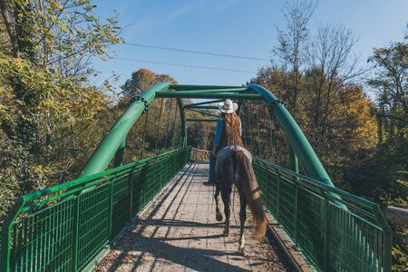 horse blonde: Pretty blonde girl riding her grey horse while crossing a bridge