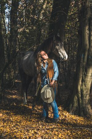 horse blonde: Pretty blonde girl standing by her grey horse in the countryside