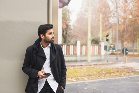 lonely man: Portrait of a young handsome Indian man texting in an urban context