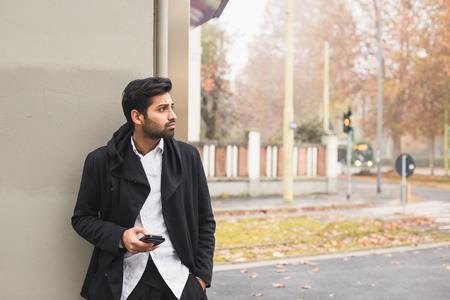 hombre solitario: Retrato de un joven hermoso texto de hombre indio en un contexto urbano