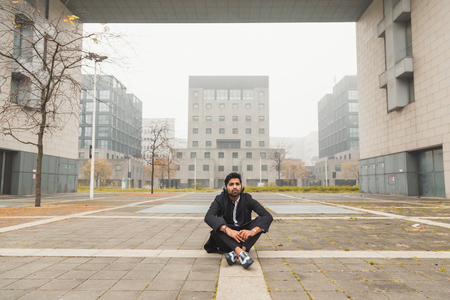 indian style sitting: Portrait of a young handsome Indian man with headphones listening to music in an urban context