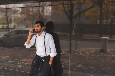 unhappy man: Portrait of a young handsome Indian man talking on phone in an urban context