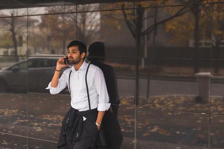 mirada triste: Retrato de un hombre indio guapo joven hablando por teléfono en un contexto urbano