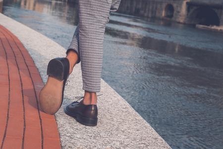 estilo urbano: Detalle de los zapatos de un joven y guapo modelo asi�tico que presenta por una cuenca artificial urbana Foto de archivo