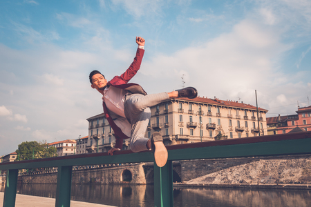 balustrade: Young handsome Asian model dressed in red blazer jumping a balustrade