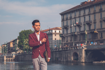 philippine adult: Young handsome Asian model dressed in red blazer posing by an rtificial basin