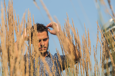 cool guy: Young handsome man with short hair posing in a field Stock Photo