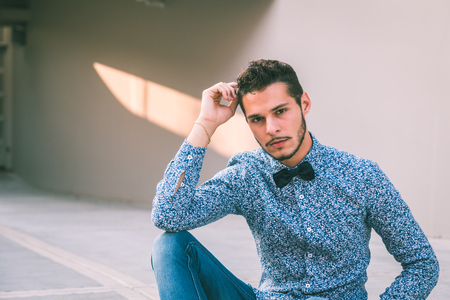 hair tie: Young handsome man with short hair wearing a bow tie and posing in the city streets Stock Photo