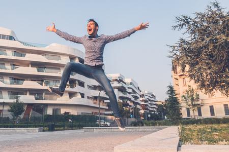 짧은 머리를 가진 젊은 잘 생긴 남자 나비 넥타이를 착용하고 도시의 거리에서 점프