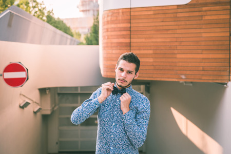 cool guy: Young handsome man with short hair wearing a bow tie and posing in the city streets Stock Photo