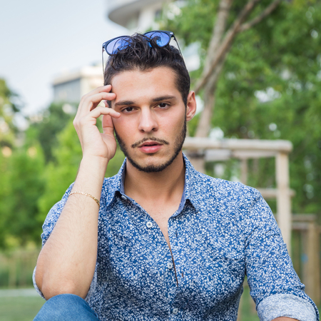 cool man: Young handsome man with short hair sitting on a bench in a city park