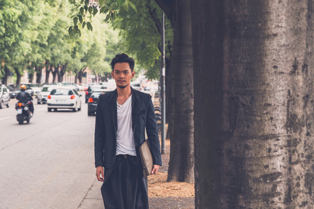philippine adult: Young handsome Asian model dressed in black posing in the city streets Stock Photo